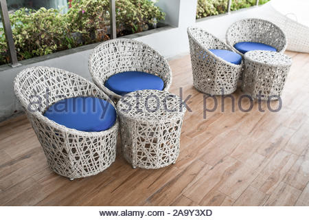wicker white and blue chairs and white tables on the terrace - Stock Photo