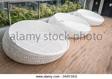 Three round  white rattan chairs on the patio in the resort - Stock Photo