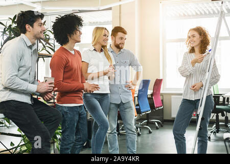 Female team leader making presentation for colleagues in office Stock Photo