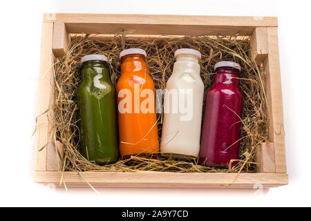 Set of healthy colored detox drinks in wooden box on white - Stock Photo