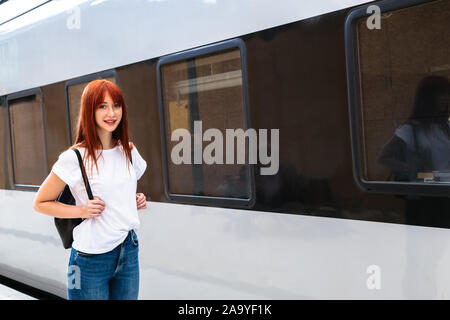 Young girl on railway platform near suburban train - Stock Photo