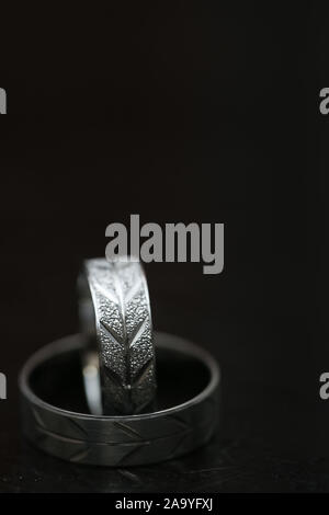 Two wedding rings on dark wooden surface with blurred background - Stock Photo