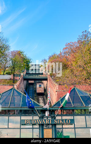 Budapest, Hungary - Nov 6, 2019: Cable car, public funicular train leading to the Buda Castle in the Hungarian capital. Tram tracks in the narrow corridor leading uphill. Vertical photo. - Stock Photo