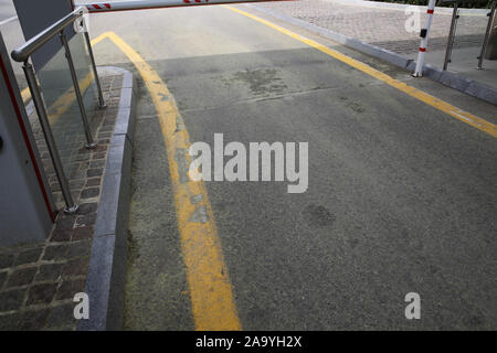 the road under the barrier. The road is covered with yellow . Barrier on the car parking . - Stock Photo
