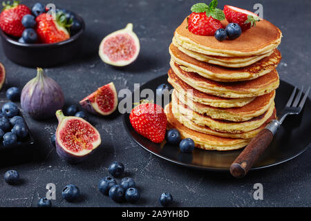 stack of almond flour healthy pancakes on a black plate with figs, strawberries, blueberries and mint, horizontal view from above. close-up - Stock Photo