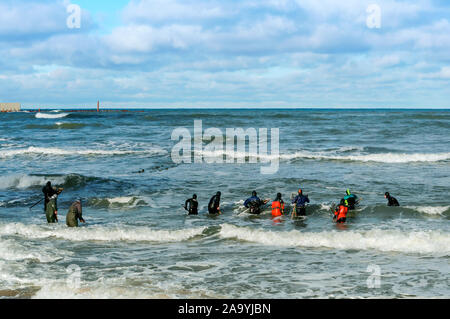 extract amber from the sea, amber catchers in the waves of the sea, Baltic sea, Kaliningrad region, Russia, 28 October 2018 - Stock Photo