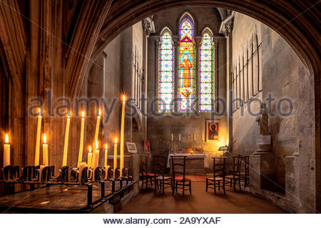 Saint-Antoine-l'Abbaye abbey church : candles in front of the Blessed Sacrament chapel - Stock Photo