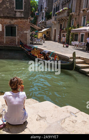 A girl sits on the steps by a Venetian canal with a gondola opposite: Rio del Megio and Calle Larga, Santa Croce, Venice, Italy - Stock Photo
