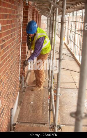 A person wearing safety gear and standing on a scaffold, uses a spray gun while working on the exterior of Gilman Hall, on a cold day at the Johns Hopkins University, Baltimore, Maryland, March 11, 2009. From the Homewood Photography Collection. () - Stock Photo