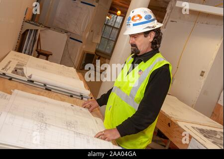 A construction worker reviews blueprints during restoration of the historic Gilman Hall at the Johns Hopkins University in Baltimore, Maryland, April 14, 2009. From the Homewood Photography collection. () - Stock Photo