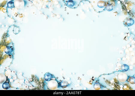 Christmas composition with fir branches, baubles and decorations on blue background. Flat lay, New Year frame. - Stock Photo