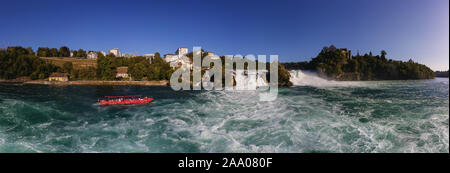 Roaring waterfall in Switzerland at a sunny afternoon. A red tourist boat fights the stream in the blue glacier water - Stock Photo