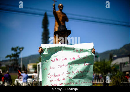 San Salvador, El Salvador. 18th Nov, 2019. A man holds up a banner that reads asking Nayib Bukele president of El Salvador to condemn the coup d'etat in Bolivia against former president Evo Morales while a group of Salvadorans protest Credit: Camilo Freedman/ZUMA Wire/Alamy Live News - Stock Photo