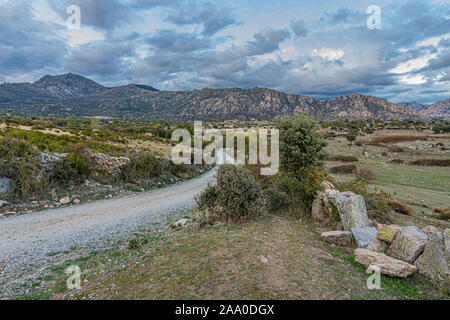 landscape with rural road fields with its hills and in the background the Sierra de Guadarrama a cloudy day. madrid Spain - Stock Photo