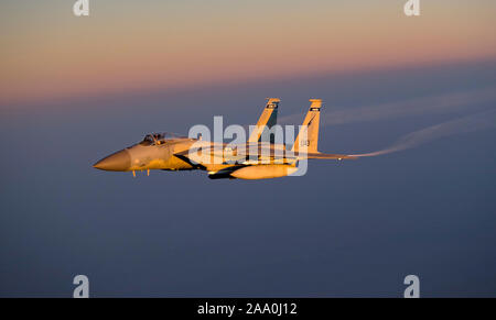 A U.S. Air Force F-15C Eagle conducts a combat air patrol mission over an undisclosed location in Southwest Asia, Sept. 3, 2019. The F-15C plays a key role in Air Force Central Command operations by maintaining constant readiness in support of air operations by providing deterrence and stability and bolstering the mission efforts of coalition partners. - Stock Photo