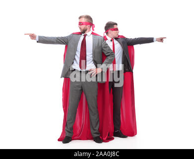 two businessmen in superhero raincoats pointing in different directions. - Stock Photo