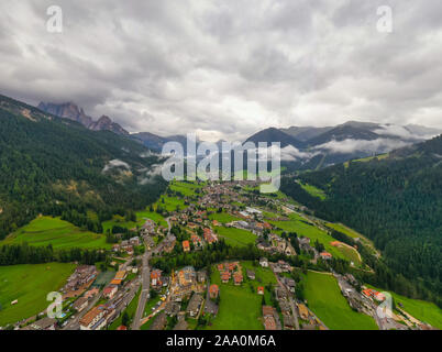 Beautiful aerial panoramic view of the Dolomites Alps, Italy. Mountains covered by clouds and fog. Catinaccio mountain ranges. Fassa Valley, Val di
