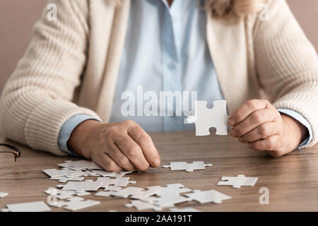 cropped view of retired woman with alzheimer holding puzzle piece