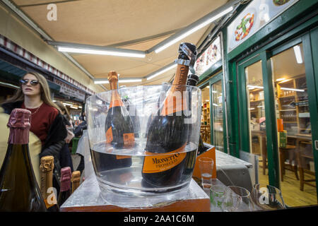 VIENNA, AUSTRIA - NOVEMBER 6, 2019: Prosecco bottles on display in an ice bucket in a Vienna market with people tasting the wine behind. Prosecco is a - Stock Photo