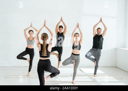 back view of yoga trainer standing in front young people practicing tree pose - Stock Photo