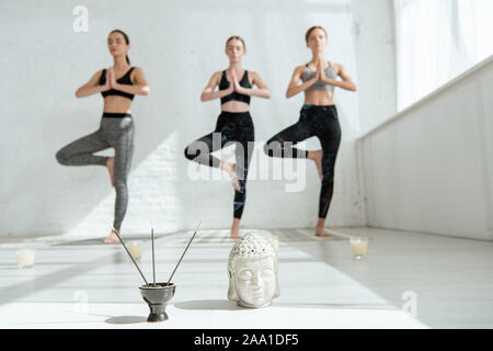 selective focus of Buddha head sculpture, incense sticks, and three women standing in tree pose - Stock Photo