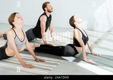 three women practicing the cobra pose during yoga class at