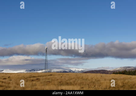 A small Telecommunications repeater pylon, high up in the Angus Glens on Tulloch Hill, looking over the snow covered mountains to the north. - Stock Photo