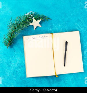 New Year resolutions, a square overhead flat lay shot with handwriting and a place for text, on a blue background with a pen, a Christmas tree branch - Stock Photo