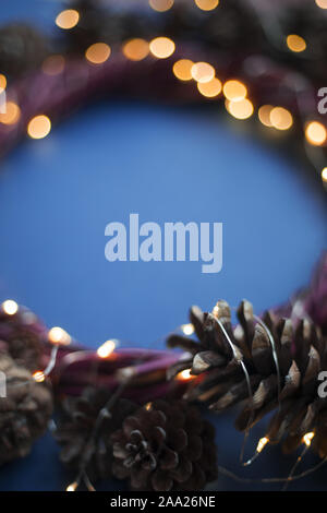 Christmas wreath of pine cones and glowing lights garland on blue background copy space text - Stock Photo