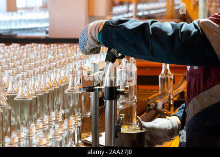 Glassworks. Glass industry. Working hands hold a glass bottle on the background of a conveyor belt. - Stock Photo