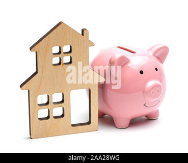 Pink piggy bank and wooden house isolated on white background. Saving money to buy a house or saving money when buying a property on credit. - Stock Photo
