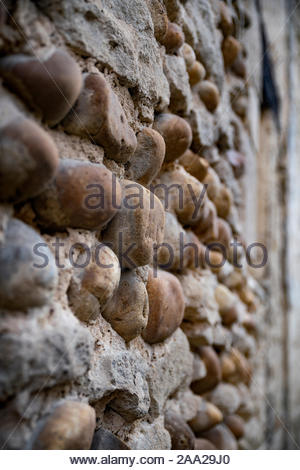 Medieval pebble stone wall in Saint-Atoine-l'Abbaye (France) - Stock Photo