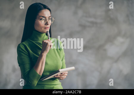 Photo of interested pondering woman thoughful thinking on her future plans holding notepad isolated grey wall concrete color background - Stock Photo