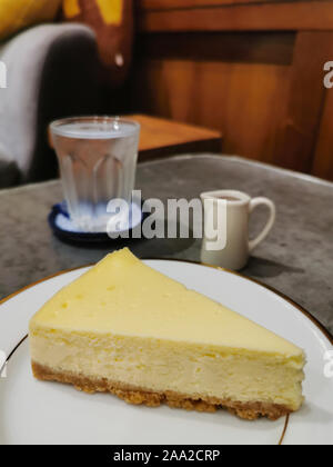 slice of plain traditional new york cheesecake on the white plate ready to serve in the bakery shop. - Stock Photo