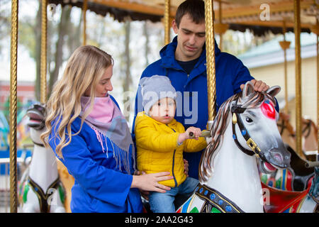Mom and dad with the baby on the carousel.Family resting in the park.Parents with a little son - Stock Photo