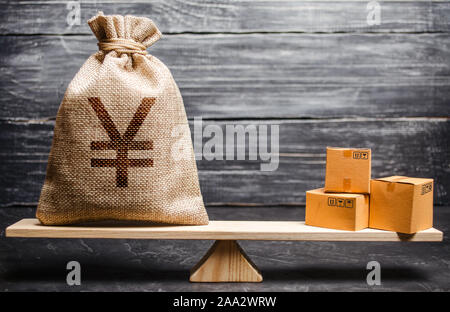 Yen yuan symbol money bag and a bunch of boxes on scales. Trade exchange balance. Import and export, economic processes. Profit from manufactured good