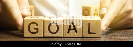 Businessman puts wooden blocks with the word Goal. The concept of achieving business goals. Reaching new heights. Execution of a business plan. Purpos Stock Photo