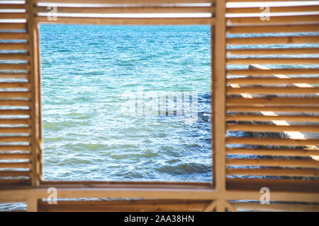 A square window overlooking the sea from a wooden house with cracks. Traveling in nature. - Stock Photo