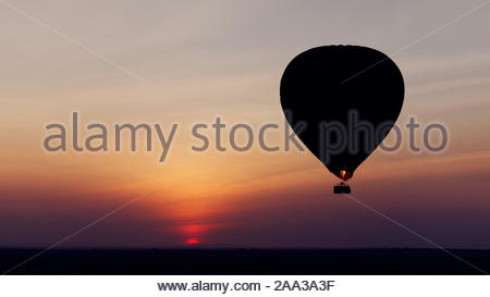 first rays of rising sun and silhouette of another hot air ballon seen on savannah plain view from hot air balloon safari - Stock Photo