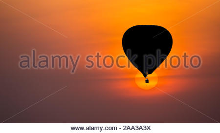 Silhouette of a hot sir nalloon on safari against a perfect round rising orange sun background - Stock Photo