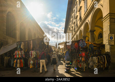 Backlight view of the street market in San Lorenzo district in the historic centre of Florence with people in a sunny autumn day, Tuscany, Italy