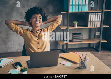 Photo of corporate cheerful positive ceo in yellow shirt smiling toothily dreaming thoughtful looking away relaxing after hard-working day - Stock Photo