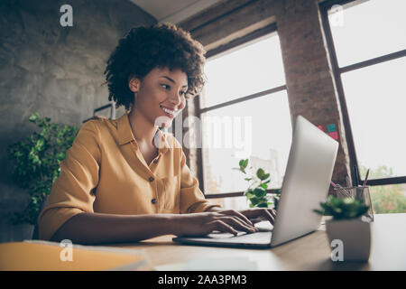Photo of cheerful positive business lady smiling toothily looking into screen of notebook computer comparing corporate income for previous year with