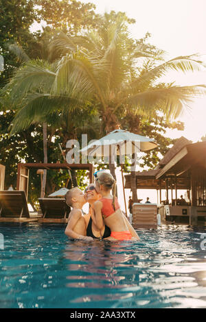Adorable little brother and sister kissing their mom while playing together in a tropical resort swimming pool on a sunny day - Stock Photo