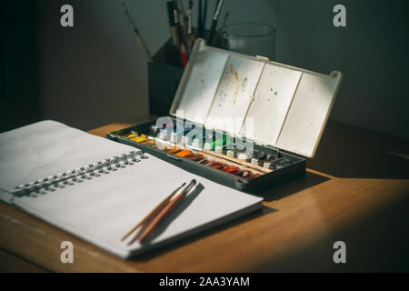 The artist's workplace on the table, where watercolors, sketchbook and brushes lie, is illuminated by a beam of sunlight that cuts through the darknes - Stock Photo