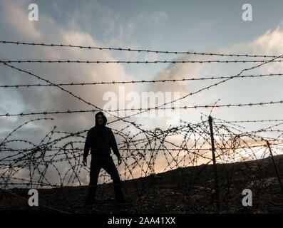Man wearing hoodie behind barbed wire, razor wire fence. - Stock Photo