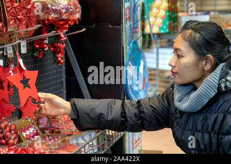 A young woman chooses Christmas decorations at the store. Purchase of Christmas decorations in the supermarket. - Stock Photo