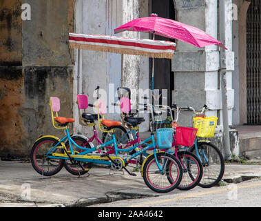 PENANG, MALAYSIA, NOV 12 2017, Colorful bicycles with umbrellas for tourists parked on the city street. - Stock Photo