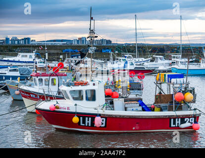 Small fishing boats moored in Newhaven Harbour at sunset on a Winter day, Edinburgh, Scotland, UK - Stock Photo