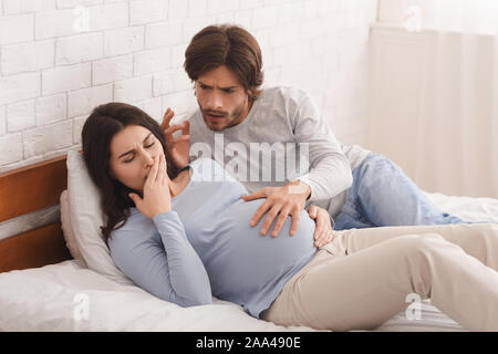 Pregnant woman suffering from morning nausea, worried husband soothing her. - Stock Photo